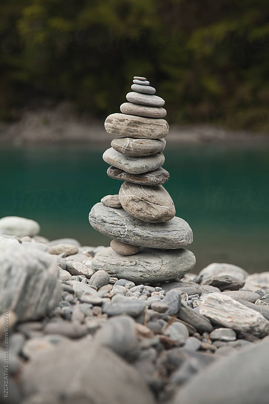 A tower of stones piled up at the edge of a river. by RZ CREATIVE for Stocksy United