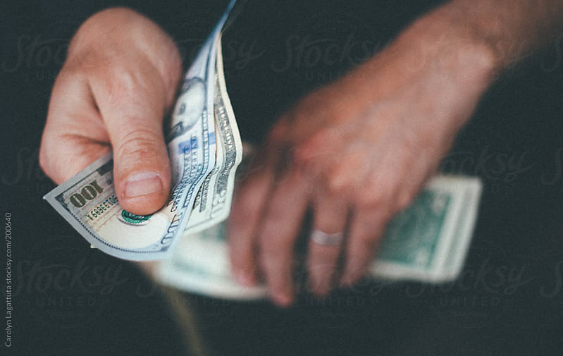 Man's hands holding and counting cash by Carolyn Lagattuta for Stocksy United