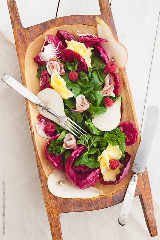 Winter salad with radicchio, field salad, pears, cheese, pancetta and raspberries by Elisabeth Coelfen for Stocksy United