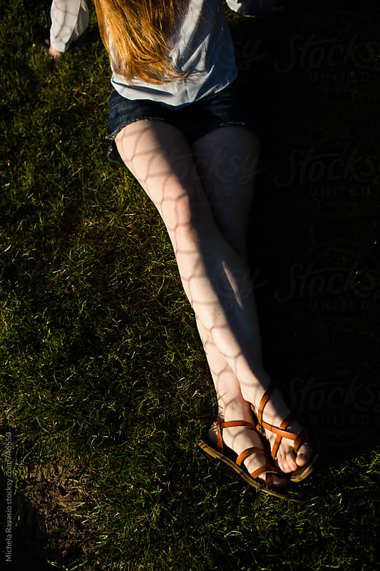 Shadow of a fence on the female legs by michela ravasio for Stocksy United