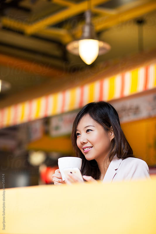 Beautiful Asian woman holding a coffee cup inside a cafe by Suprijono Suharjoto for Stocksy United