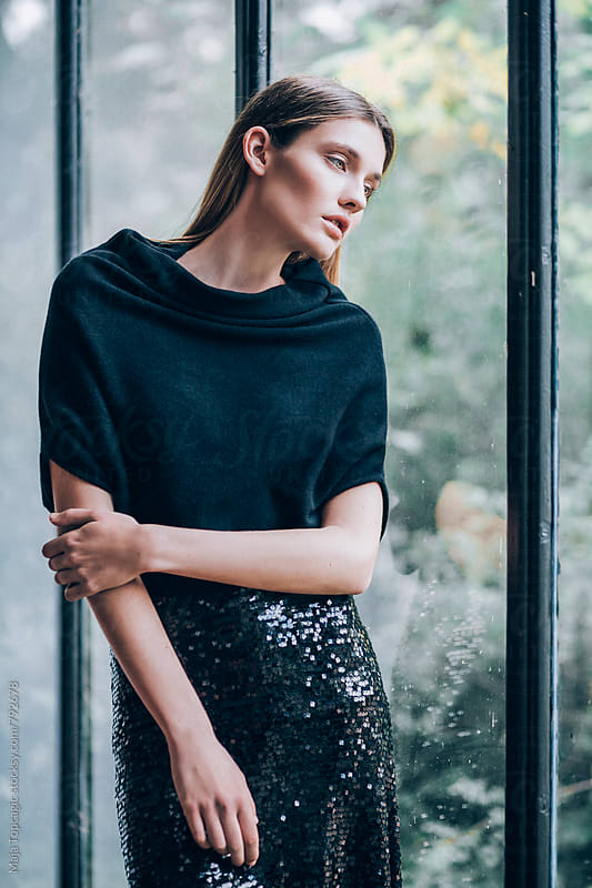 Beautiful woman in a dress leaning on a window by Maja Topcagic for Stocksy United