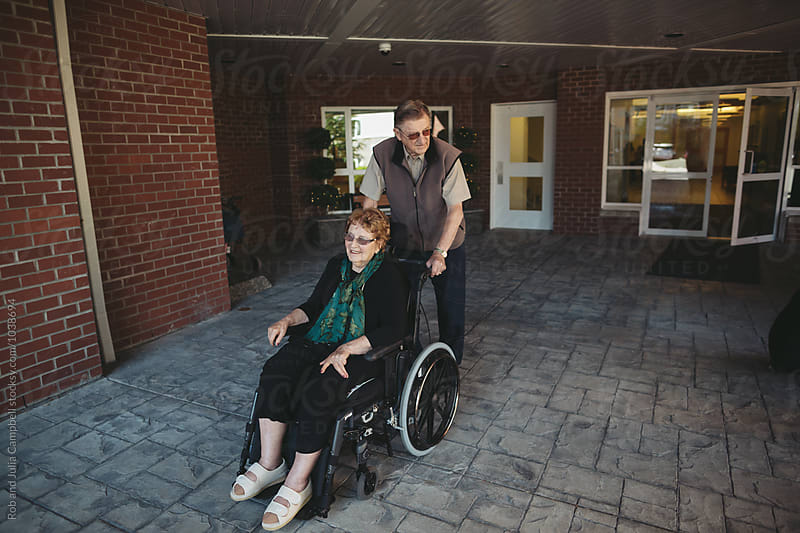 Caring caucasian man pushing woman in wheechair outside by Rob and Julia Campbell for Stocksy United