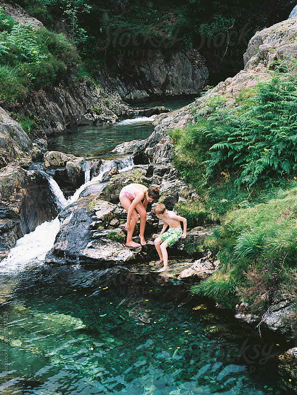 children playing in water pools in the mountains by Léa Jones for Stocksy United