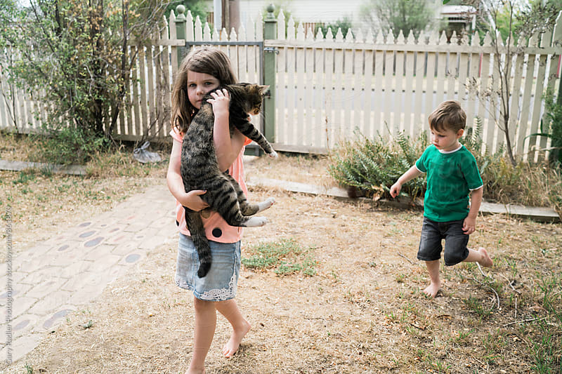 Girl Carrying Cat while Boy Follows