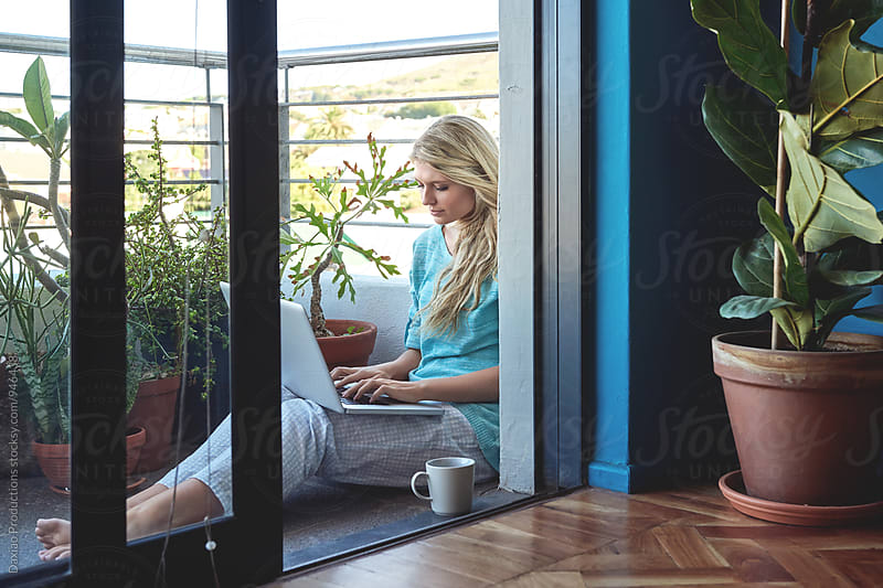 beautiful young woman working outdoors on her laptop at home on the balcony by Daxiao Productions for Stocksy United