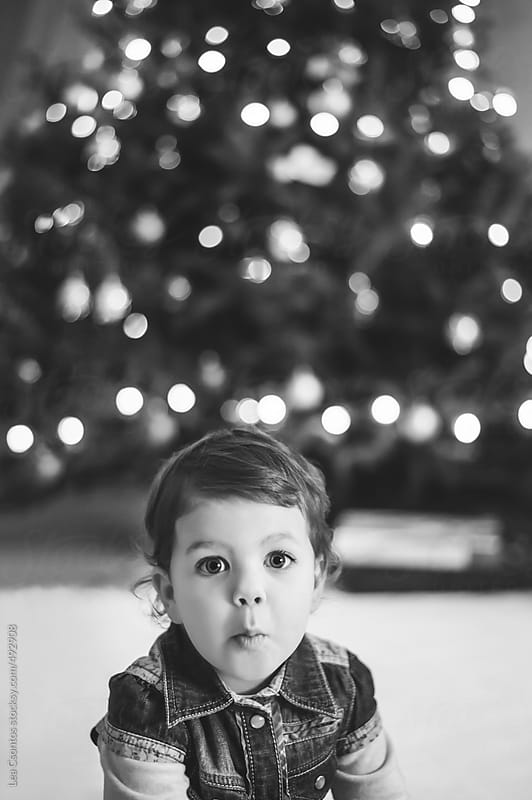 Child in front of an out-of-focus christmas tree making a funny, surprised face by Lea Csontos for Stocksy United