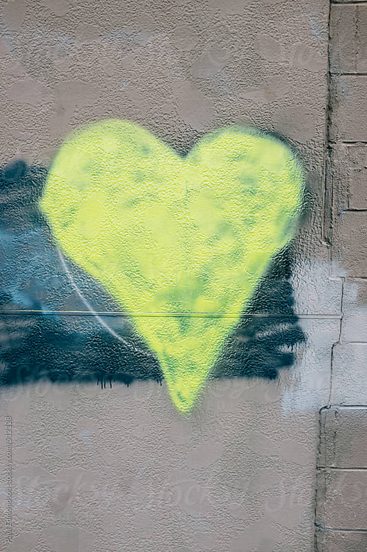 Yellow heart shape painted on wall of building by Paul Edmondson for Stocksy United