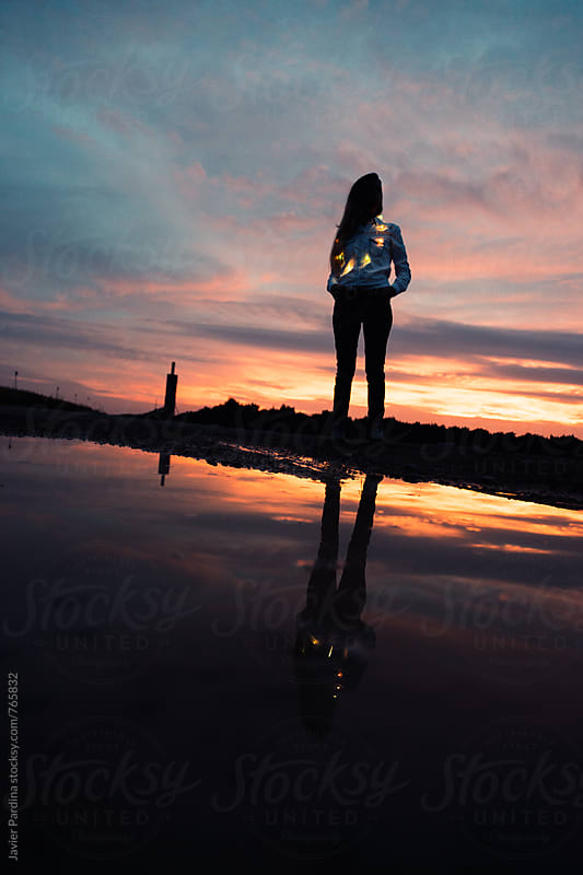 reflection of  girl with light at sunset by Javier Pardina for Stocksy United