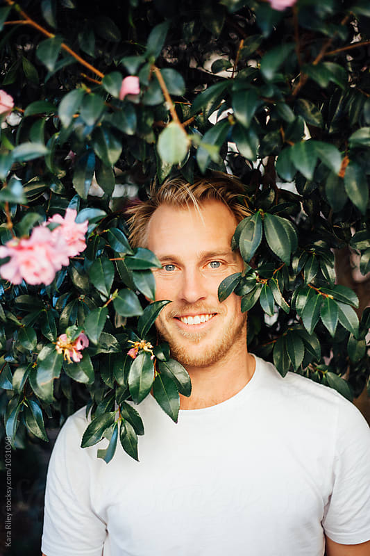 Blonde man in Flower Bush by Kara Riley for Stocksy United