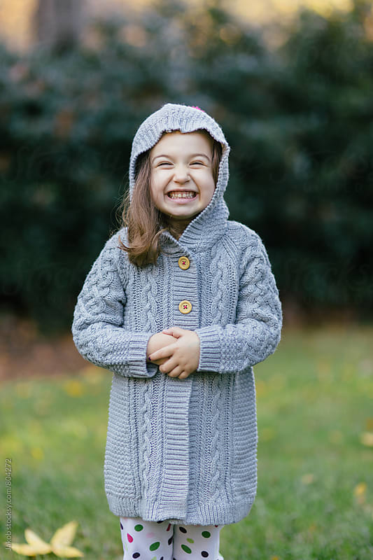 Cute young girl wearing a cardigan with a hood making funny faces by Jakob for Stocksy United