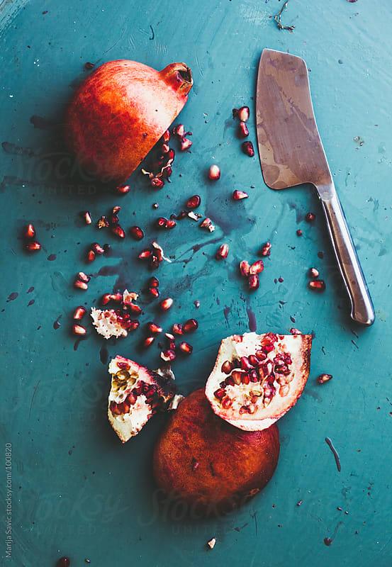 Sliced Pomegranate on Blue Metal Plate by Marija Savic for Stocksy United