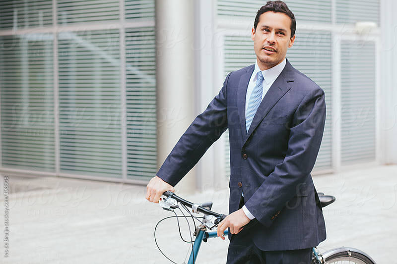 Young business man in suit with his bike by Ivo de Bruijn for Stocksy United