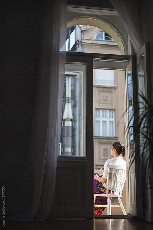 Woman Sitting on the Balcony by Lumina for Stocksy United