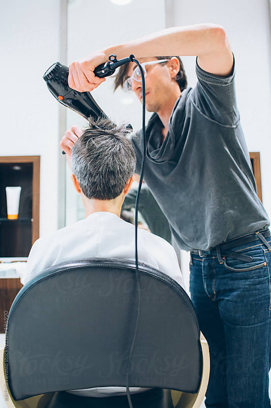 Hairdresser drying woman's hair by michela ravasio for Stocksy United