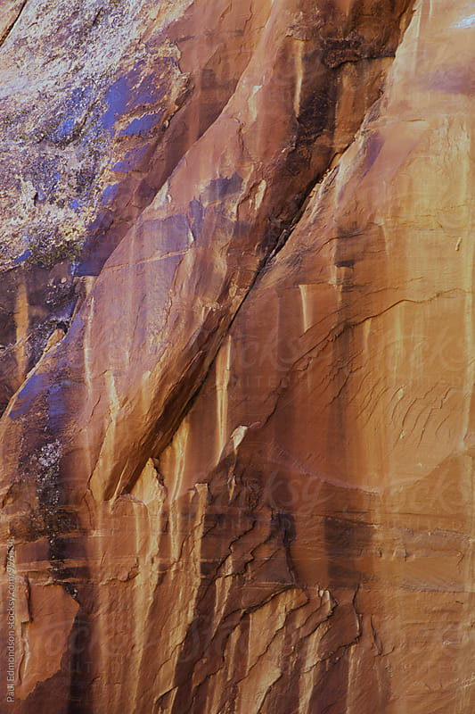 Stained sandstone walls in Coyote Gulch by Paul Edmondson for Stocksy United