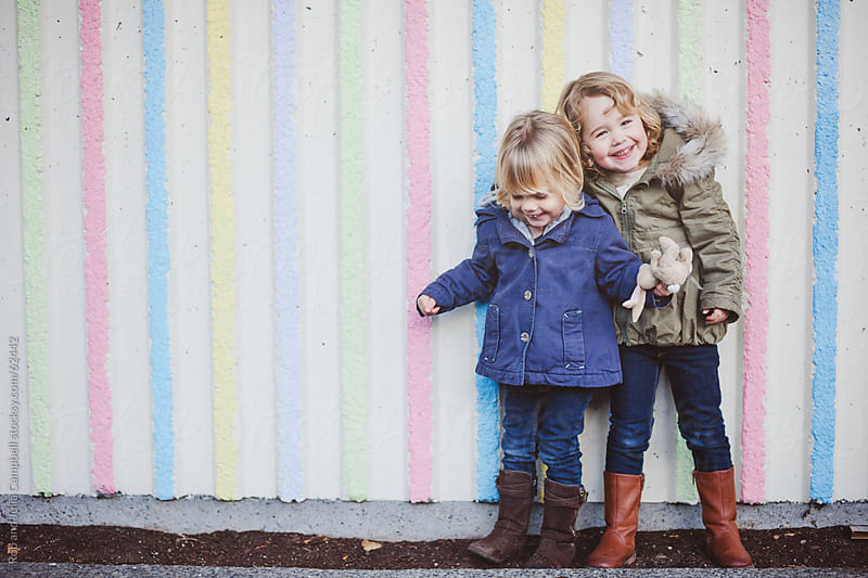 Cute, young sisters having fun downtown in front of coloured wall by Rob and Julia Campbell for Stocksy United