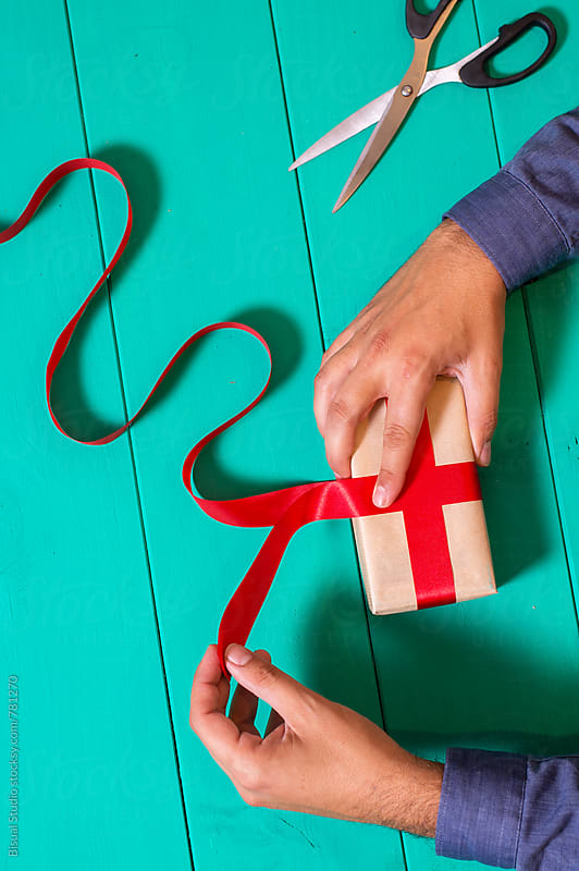 Man wraping a christmas present  by Bisual Studio for Stocksy United