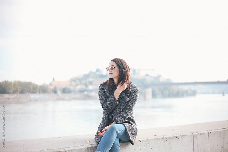 Stylish woman sitting on a quay during the day  by Marija Mandic for Stocksy United
