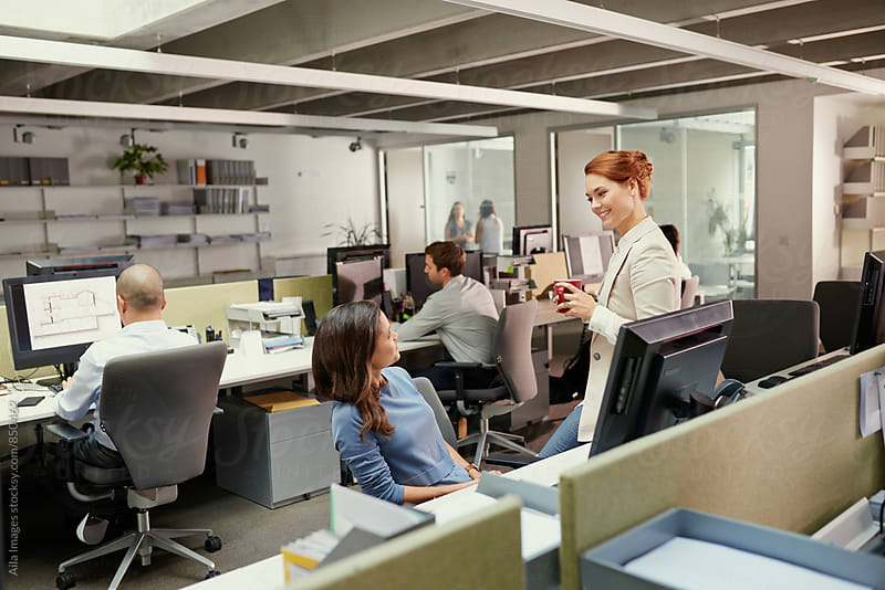 Redhead woman leaning against desk facing business woman by Aila Images for Stocksy United