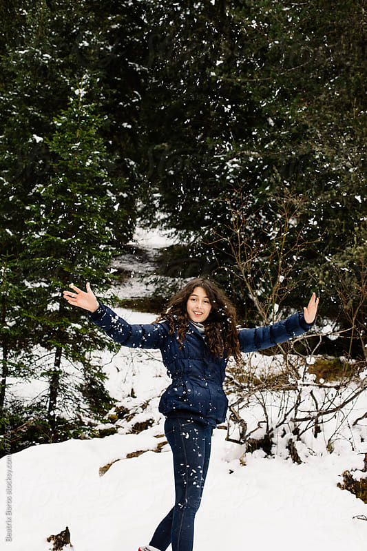 Happy girl with a joyful smile while it's snowing in the forest by Beatrix Boros for Stocksy United