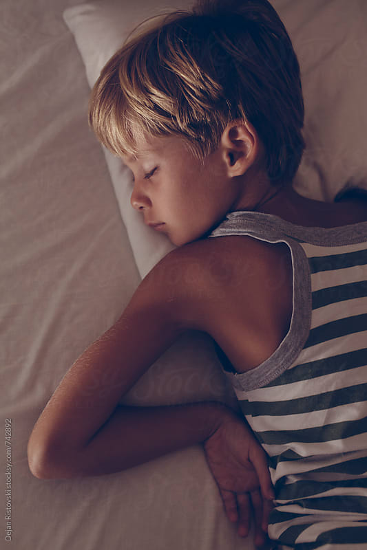 Boy sleeping in bed by Dejan Ristovski for Stocksy United