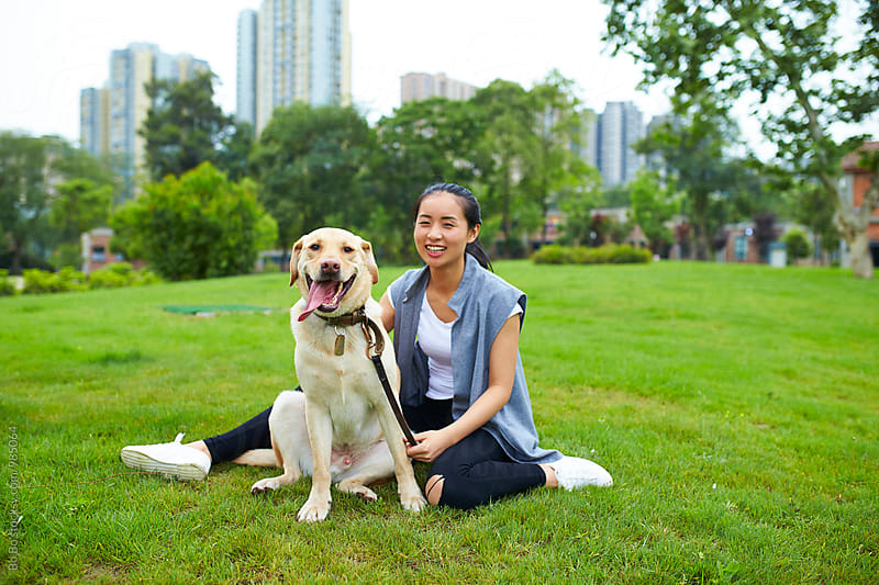young asian woman with her dog on the lawn by Bo Bo for Stocksy United