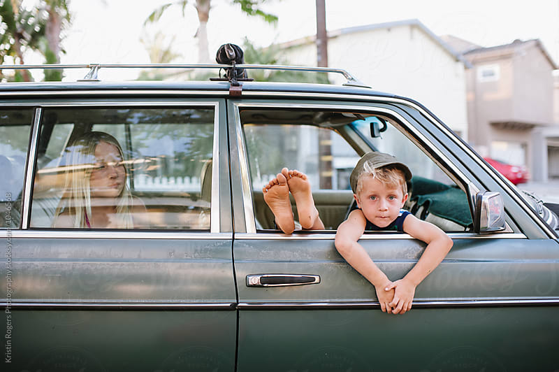 Cute kids hanging out in car and peeking out the window of an old car by Kristin Rogers Photography for Stocksy United