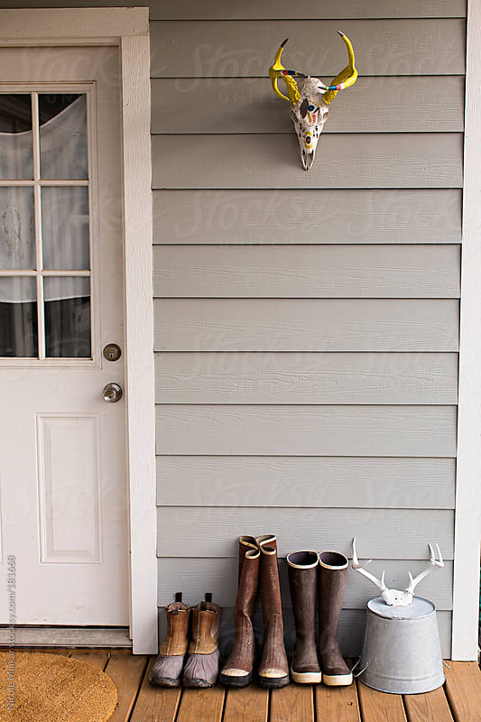 Rubber boots lined up outside on the back porch by Nicole Mlakar for Stocksy United