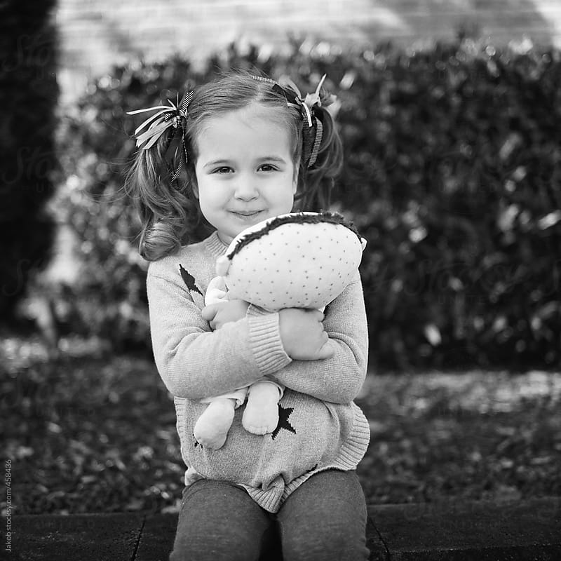 A toddler holding her favorite stuffed animal by Jakob for Stocksy United