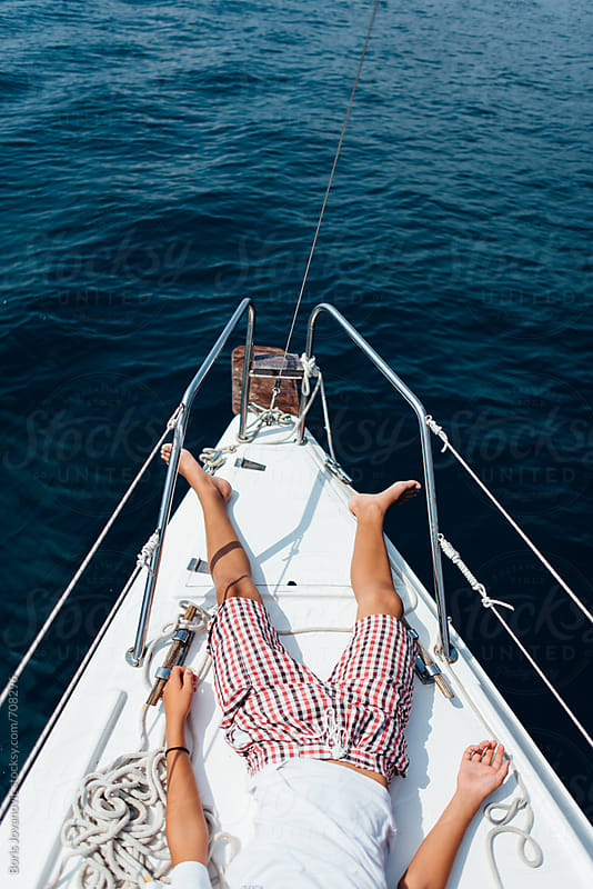 Young boy having a rest on the bow of the ship by Boris Jovanovic for Stocksy United