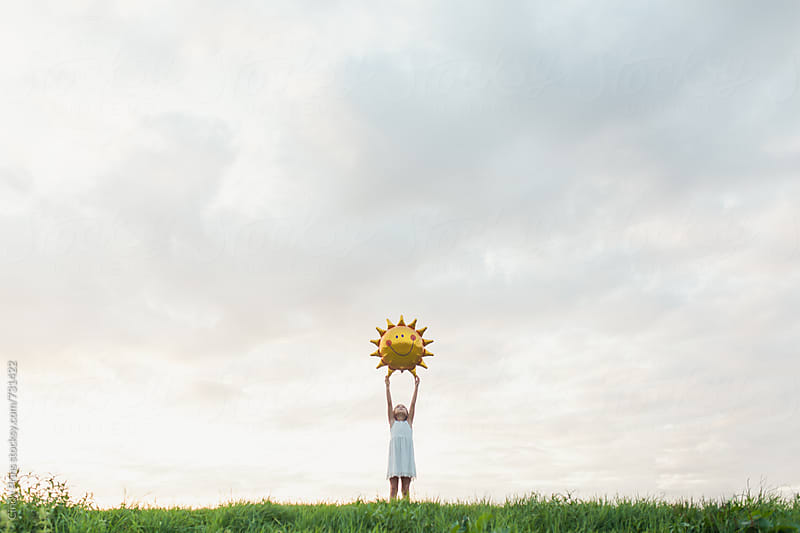 Little girl with a big sun balloon against a cloudy sky by Cindy Prins for Stocksy United
