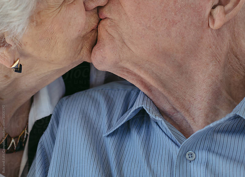 Kiss between wrinkled senior couple  by Rob and Julia Campbell for Stocksy United