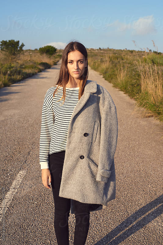 woman with grey coat on her shoulder by Guille Faingold for Stocksy United