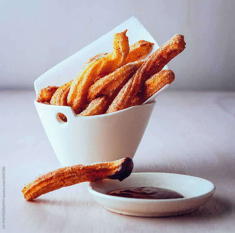 Churros with chocolate sauce by J.R. PHOTOGRAPHY for Stocksy United