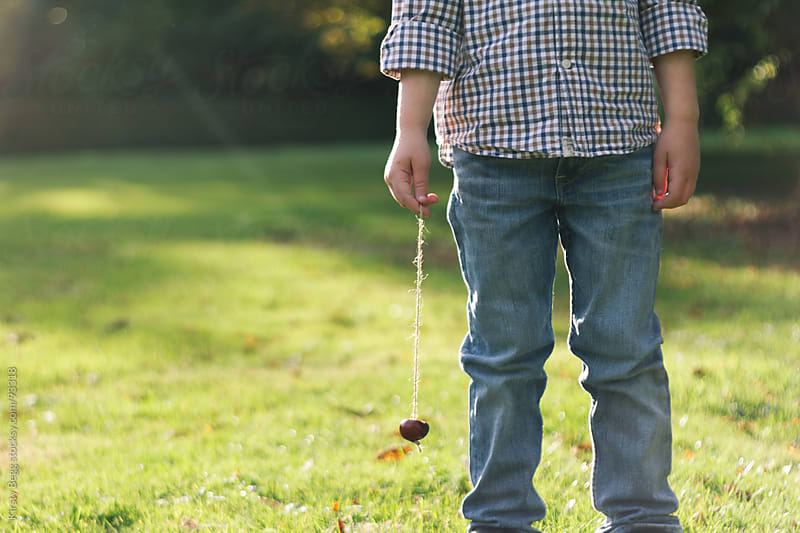 Boy holding conker on string by Kirsty Begg for Stocksy United