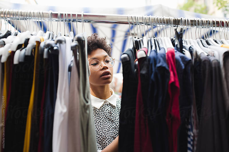 Young woman browsing through dresses at the marketplace by michela ravasio for Stocksy United
