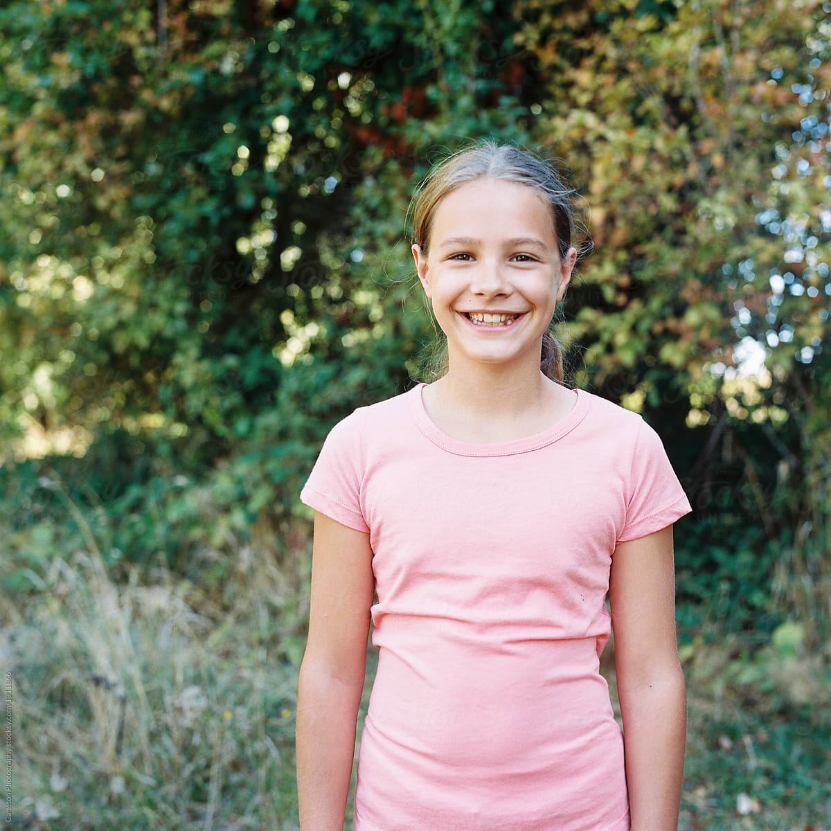 Preteen girl smiling outdoors by Carleton Photography