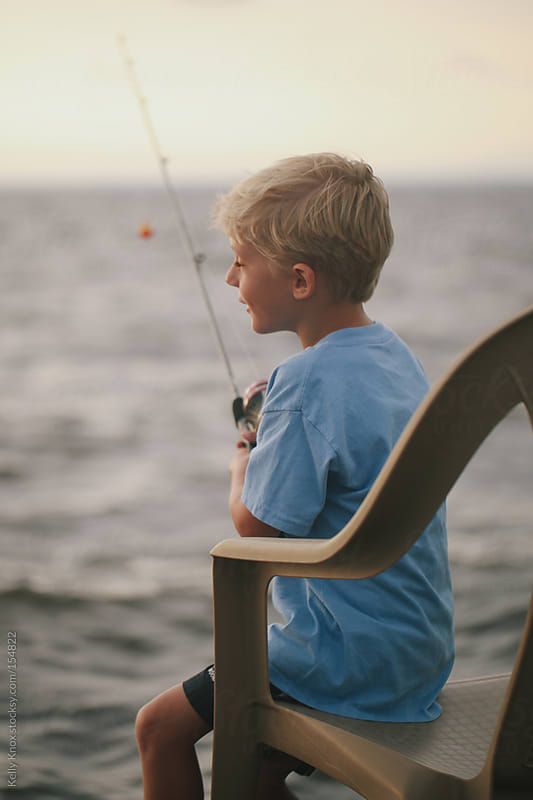 boy fishing at the end of the day by Kelly Knox for Stocksy United