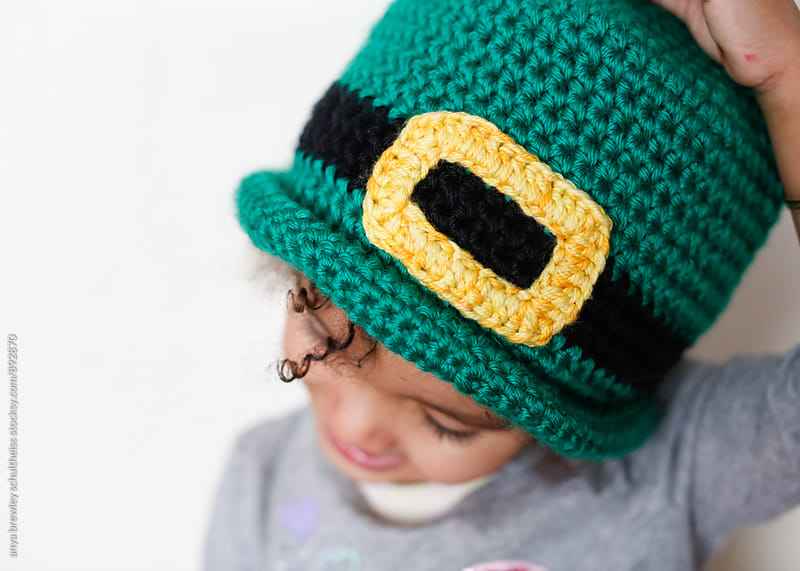 Close up portrait of young girl wearing a handmade crochet leprechaun hat by anya brewley schultheiss for Stocksy United