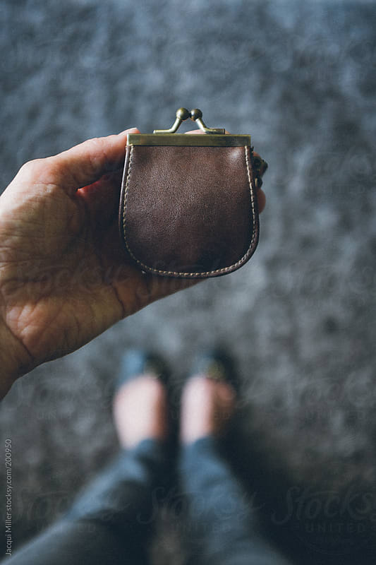 Woman's hand holding a vintage coin purse. by Jacqui Miller for Stocksy United