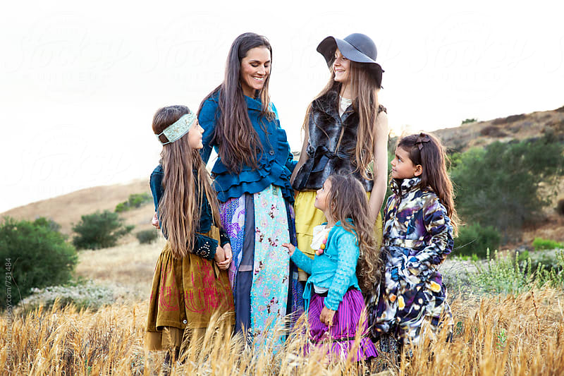 Mother and four daughters smiling surrounded by nature by Curtis Kim for Stocksy United