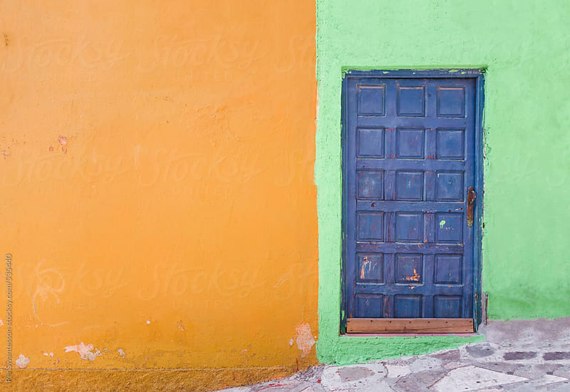 Colorful wall with blue door in Guanajuato, Mexico by Per Swantesson for Stocksy United
