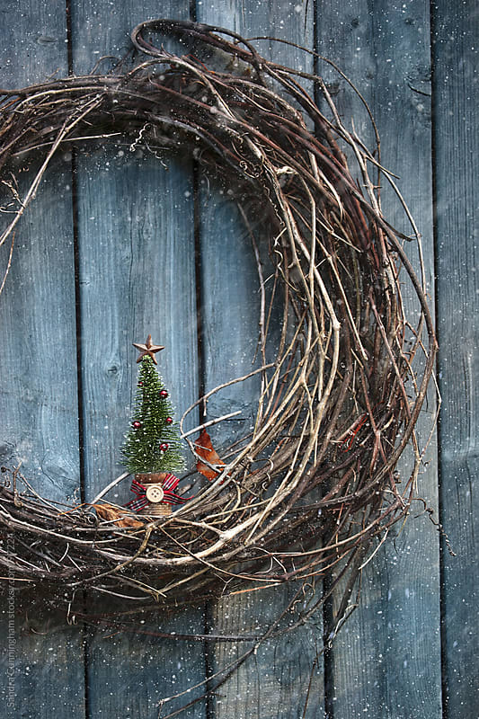 Old wreath with small tree ornament on barn wall by Sandra Cunningham for Stocksy United