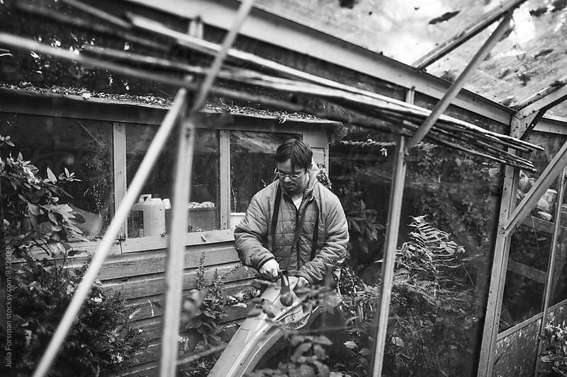 Black and white of man with Down's syndrome clearing leaves in a garden. by Julia Forsman for Stocksy United