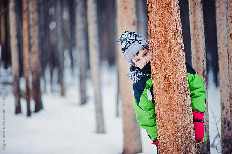 Boy peeking out from behind a pine tree in the snow by Angela Lumsden for Stocksy United