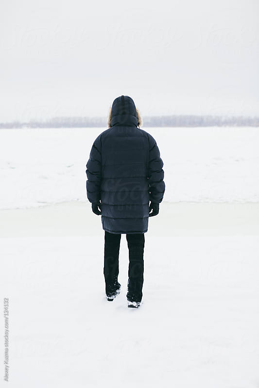 man walking on the frozen river by Alexey Kuzma for Stocksy United