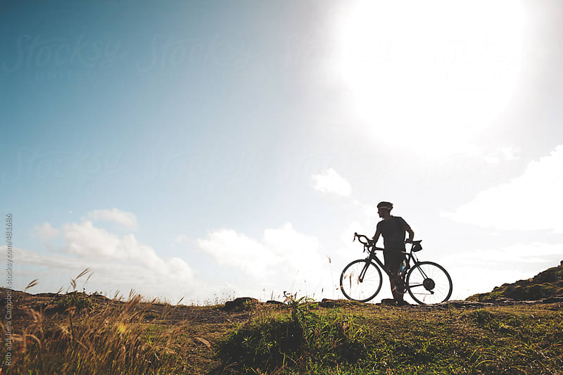 Silhoutte of young active cycle man standing near road - looking at view by Rob and Julia Campbell for Stocksy United