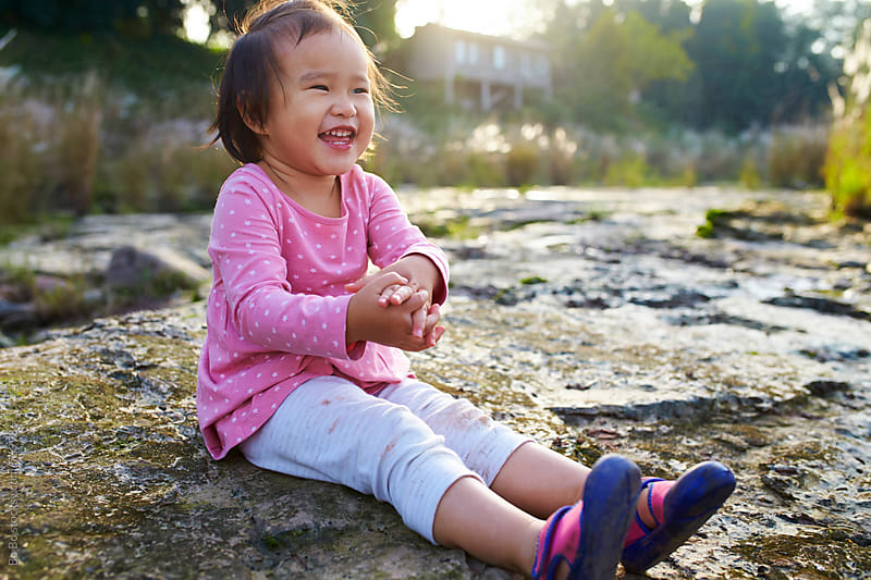 happy little asian girl sitting on the rock outdoor by Bo Bo for Stocksy United