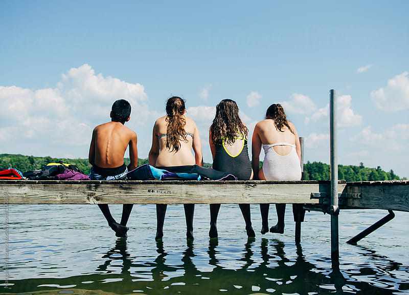 four teenagers sit at the end of a dock by Margaret Vincent for Stocksy United